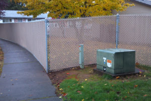 Chain Link Fencing With Tan Vinyl Slats For Added Privacy - Sandy